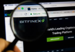 Bitfinex logo on a computer screen with a magnifying glass