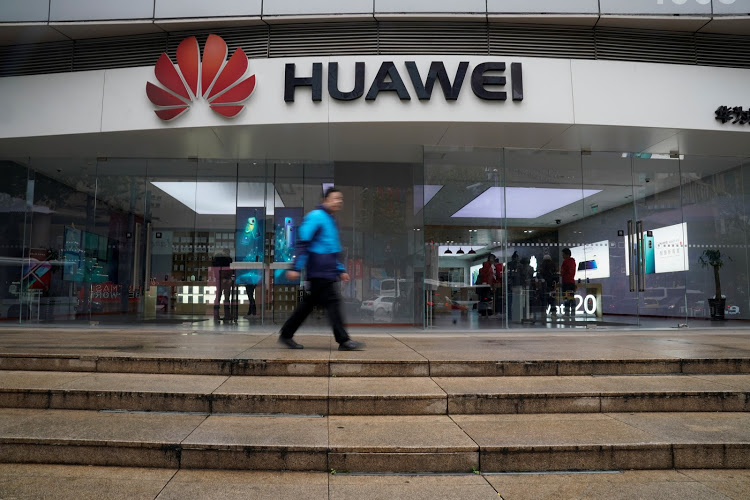 A man walks by a Huawei logo at a shopping mall in Shanghai, China December 6, 2018. REUTERS/Aly Song