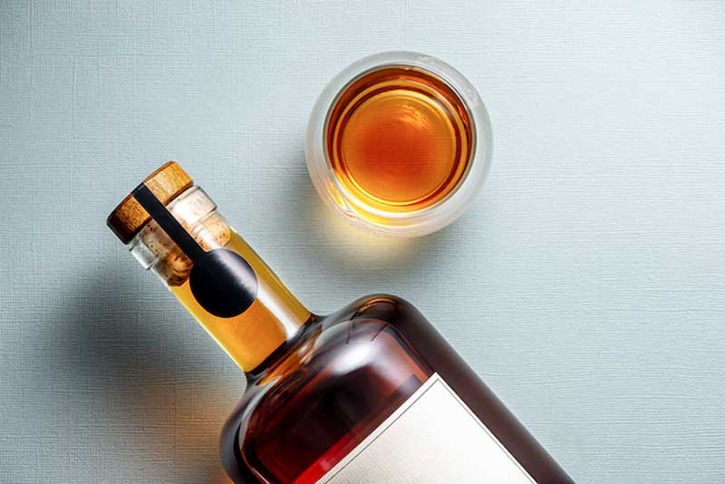 A light colored background, top-down, with a blank-label whiskey bottle and an amber liquid poured into a glass.