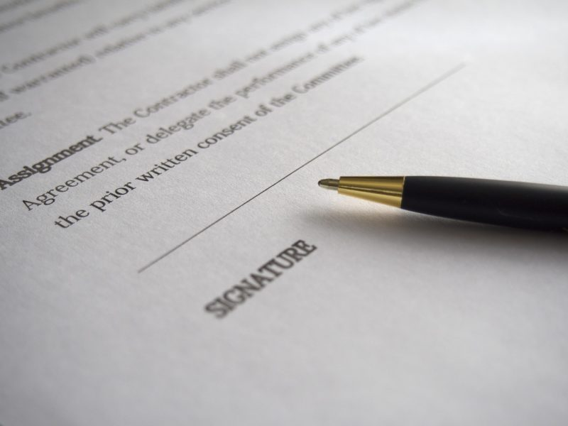 Legal document on white paper with words suggesting a contract, line for a signature, with a black ball point pen laying across it.