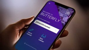 "Hand holding a smartphone with the Butterfly Protocol Dapp visible on the screen, a purple user interface displays words ""Welcome to BUTTERFLY: What do you want to do johnsmith. human?"""