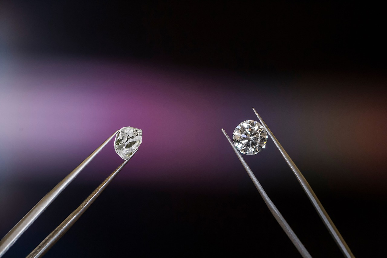 Two tweesers hold diamonds, on the left an uncut rough diamond; on the right, a brilliant, cut stone glistening with facets.